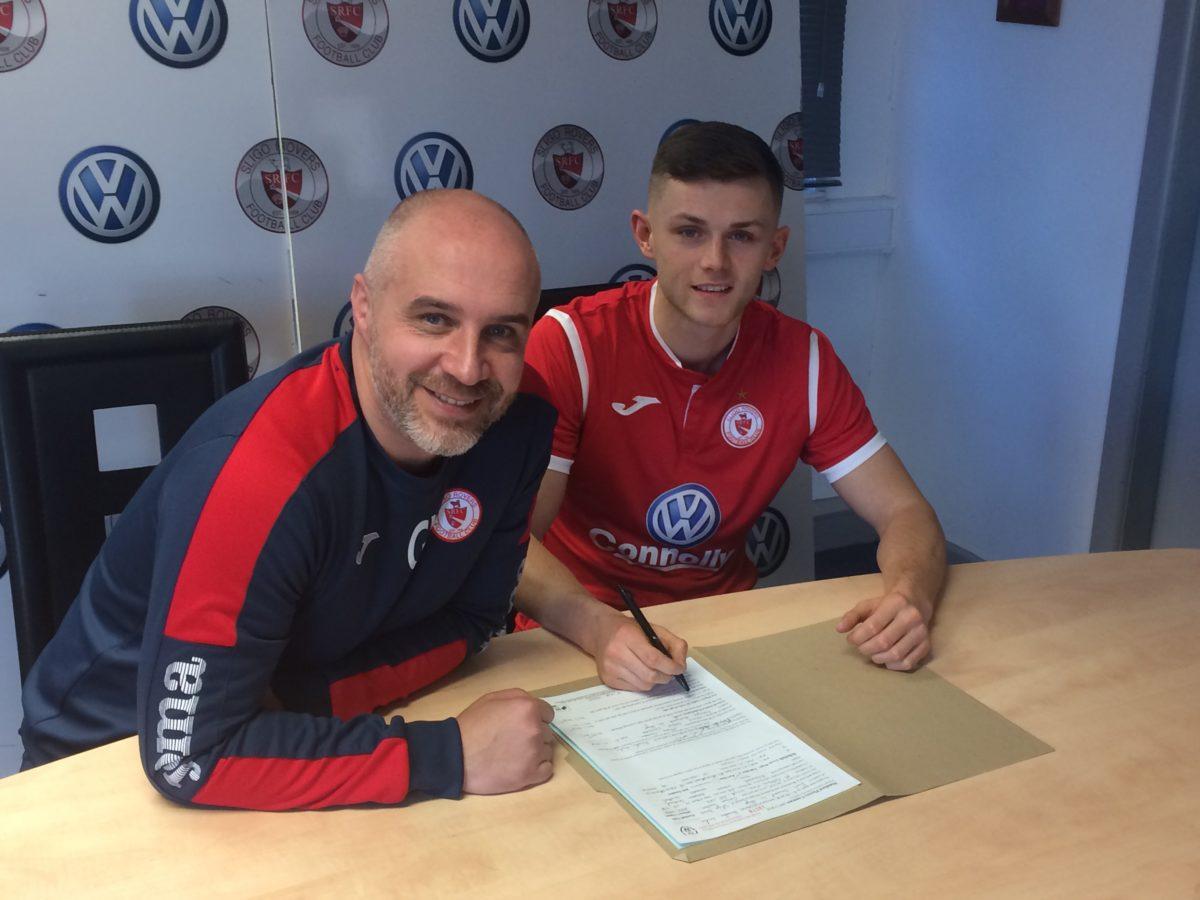 Calum Waters puts pen to paper alongside Rovers boss Gerard Lyttle.