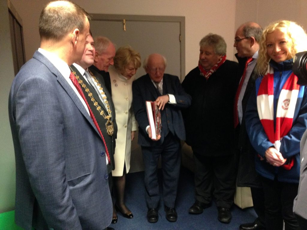 President Michael D. Higgins being presented with the book 'The Bit O'Red: A History of Sligo Rovers 1928 - 2018'